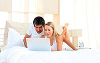 Joyful lovers using laptop lying on bed
