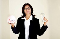 Portrait of a female model holding a piggybank and money