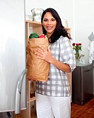 Brunette woman unpacking grocery bag