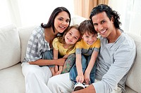Joyful family sitting on sofa