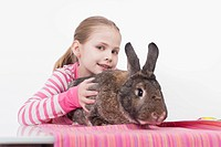 Girl holding rabbit, smiling