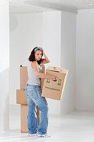 Young woman carrying on cardboard box, portrait