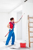 Germany, Bavaria, Young woman painting with paint roller