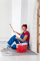 Germany, Bavaria, Young woman sitting with paint tin and paint brush, smiling, portrait
