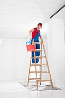 Germany, Bavaria, Young woman on step ladder and painting