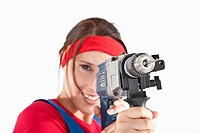 Young woman holding electric drill, portrait