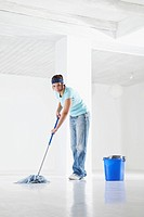 Germany, Bavaria, Young woman mopping floor, portrait