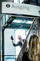 Germany, Stuttgart, Businessman showing diary to woman on stairs of office building