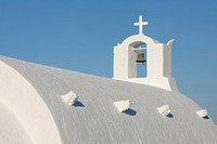 Greece, Whitewashed traditionally Greek church with bell tower and cross in Oia at Santorini