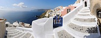 Greece, View of Oia village with cobbled path and blue gate at Santorini