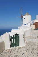 Greece, Windmill with cobbled path and green gate in traditionally Greek village Oia at Santorini