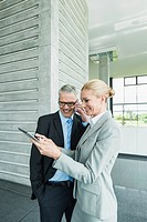 Germany, Stuttgart, Businesswoman with digital tablet while man talking on phone