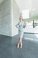 Germany, Stuttgart, Businesswoman standing with blank signs in office lobby, smiling, portrait