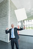 Germany, Stuttgart, Businessman holding placard in office lobby