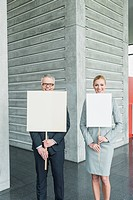 Germany, Stuttgart, Business people holding blank signs in office lobby, smiling, portrait