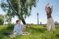 Germany, North Rhine Westphalia, Duesseldorf, Man looking at dancing woman, smiling