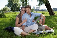 Germany, North Rhine Westphalia, Duesseldorf, Couple sitting on grass and listening music, smiling, portrait
