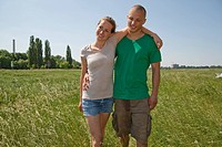 Germany, North_Rhine_Westphalia, Duesseldorf, Young couple standing on grass, smiling