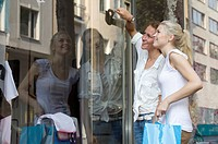 Germany, North Rhine Westphalia, Cologne, Young women at window shopping, smiling