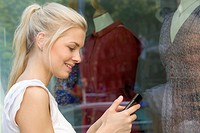 Germany, North Rhine Westphalia, Cologne, Young woman at window shopping with smart phone