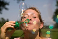 Germany, North Rhine Westphalia, Cologne, Young woman blowing soap bubbles