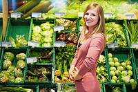 Germany, Cologne, Young woman in supermarket, smiling, portrait