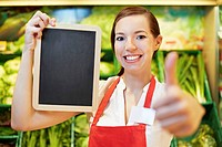 Germany, Cologne, Young woman with blackboard in supermarket, smiling, portrait