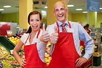 Germany, Cologne, Man and woman in supermarket showing thumbs up, smiling, portrait (thumbnail)