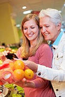 Germany, Cologne, Womens with smart phone and oranges in supermarket