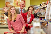 Germany, Cologne, Man and women in supermarket, smiling, portrait (thumbnail)