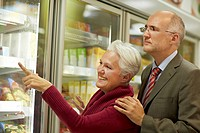 Germany, Cologne, Mature couple choosing from freezer in supermarket