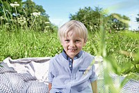 Germany, Cologne, Boy sitting on blanket in meadow, smiling, portrait