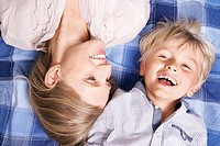 Germany, Cologne, Mother and son lying on blanket, smiling