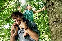 Germany, Cologne, Father carrying daughter on shoulders, smiling (thumbnail)
