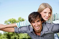 Germany, Cologne, Young couple flying, smiling, portrait