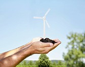 Germany, Cologne, Young man holding wind turbine with soil