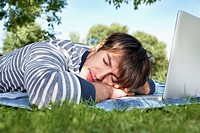 Germany, Cologne, Young man sleeping in meadow