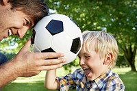 Germany, Cologne, Father and son playing with soccer ball