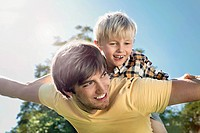 Germany, Cologne, Father and son flying, smiling