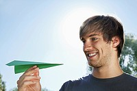Germany, Cologne, Young man holding paper plane