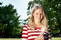 Germany, Cologne, Young woman holding lightbulb, smiling