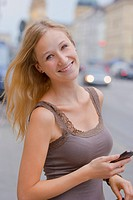 Germany, Bavaria, Munich, Young woman with smart phone in front of Bavarian State Library at Ludwigstrasse