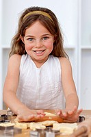 Smiling little girl baking in the kitchen