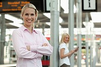 Germany, North_Rhine_Westphalica, Duesseldorf, Young businesswoman smiling, another woman with smart phone in background