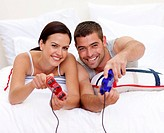 Couple having fun playing videogames in bed