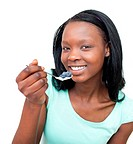 Smiling woman eating a yogurt with blueberries