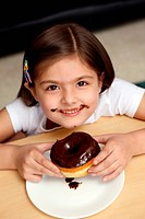 Girl eating a chocolate doughnut