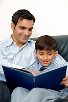Father and son sitting, reading book