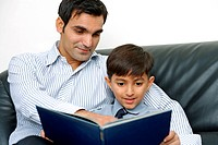 Father and son sitting reading book