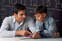 Teacher and boy in a classroom, reading a book